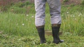 Ein Mann, der das Gras in der Gartennahaufnahme mäht stock video footage