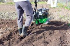 ein Mann, der das Land mit einem Motorblock, das Land für das Pflanzen von Kartoffeln vorbereitend pflügt lizenzfreies stockfoto