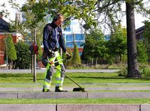 Ein Mann, der an dem Schnitt des Grases in Umea-Stadt arbeitet stockfotos