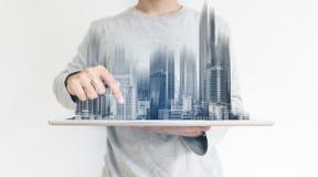 Ein Mann, der digitale Tablette verwenden, und modernes Gebäudehologramm Immobiliengeschäft und Bautechnologiekonzept lizenzfreies stockfoto