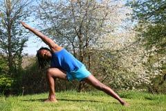 Ein Mann, der draußen eine Yogaübung tut Stockbilder