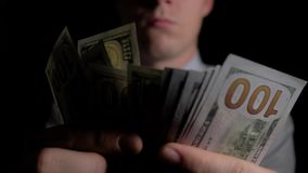Ein Mann in der Dunkelheit, die Dollar zählt Der Mann zählt die Dollar Geld in Männer ` s Händen Unerwarteter Gewinn Die Gebühr f stock footage