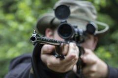 Ein Mann, der durch einen Bereich auf einem Jagdgewehr zielt stockbilder