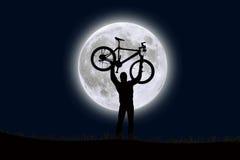 Ein Mann, der ein Fahrrad in der Front eines steigenden Mondes anhebt Stockbilder
