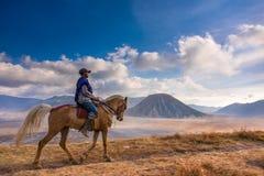 Ein Mann, der ein Pferd mit Berg Batok im Hintergrund reitet Stockbild