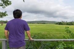 Ein Mann, der ein purpurrotes T-Shirt und eine Stellung mit seinem zurück in einer Wiese trägt Stockfotografie
