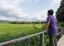 Ein Mann, der ein purpurrotes T-Shirt und eine Stellung mit seinem zurück in einer Wiese trägt Lizenzfreies Stockfoto
