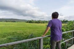 Ein Mann, der ein purpurrotes T-Shirt und eine Stellung mit seinem zurück in einer Wiese trägt Lizenzfreie Stockfotografie