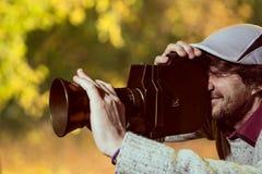 Ein Mann, der eine Kappe mit einer alten Filmkamera trägt Stockfotos