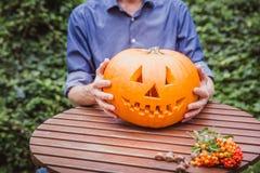 Ein Mann, der eine Laterne der Steckfassung O hält, schnitzte Halloween-Kürbis auf dem Holztisch Glückliches Halloween stockfotos