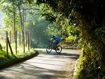 Ein Mann, der eine Mountainbike herauf einen Hügel in einer gepflasterten Straße aus der Stadt heraus reitet lizenzfreie stockfotos