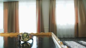 Ein Mann, der eine Uhr von der Tabelle nimmt Stockbilder