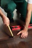Ein Mann, der an einem neuen Fußboden arbeitet Stockfotografie