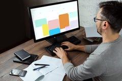 Ein Mann, ein Mann, der an einem Tisch im Büro, arbeitend auf einem Computer sitzt Das Konzept der Büroarbeit Kopieren Sie Platz stockfotos