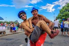 Ein Mann, der einen anderen Mann oben in seinen Armen auf dem Hintergrund der Zuckerhut während Bloco Orquestra Voadora, Carnaval Stockfoto