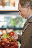 Ein Mann, der einen Apfel hält Stockbilder