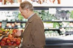 Ein Mann, der einen Apfel hält stockbild