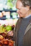 Ein Mann, der einen Apfel hält Lizenzfreie Stockfotos