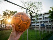 Ein Mann, der einen gelben Fußball auf einem blauen Fußballplatz hält Lizenzfreie Stockbilder