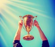 Ein Mann, der einen Goldtrophäencup als Sieger in einem Wettbewerb hält Stockfotografie