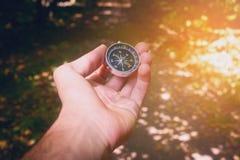Ein Mann, der einen Kompass hält und verwiesen schaut stockfotos