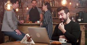 Ein Mann, der einen on-line-Anruf an seinem Laptop beim Arbeiten in einer Kaffeestube hat stock video footage
