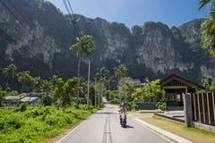 Ein Mann, der einen Roller auf die schöne Straße in Krabi-Provinz, Thailand reitet lizenzfreies stockbild