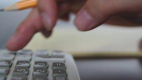 Ein Mann, der einen Taschenrechner mit Anmerkungen verwendet stock footage
