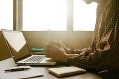 Ein Mann, der einen Tasse Kaffee hält und an Laptop in offic arbeitet Lizenzfreies Stockfoto