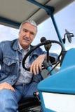 Ein Mann, der einen Traktor antreibt Lizenzfreies Stockfoto
