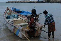Ein Mann, der fertig wird, sein Motorboot für die Fischerei anzustellen Lizenzfreie Stockbilder