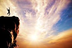 Ein Mann, der für Freude auf der Spitze des Berges springt Stockbild