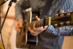 ein Mann, der Gitarre, ein wirkliches Konzert spielt, schließen herauf Gitarrenhals stockfoto