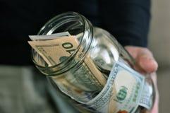 Ein Mann, der ein Glas Geld hält stockfotografie