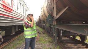 Ein Mann in der Glasarbeitskraft, die den Zug in einem Sturzhelm und in einer Uniform, gehend auf den Bahnhof sprechend am Telefo stock footage