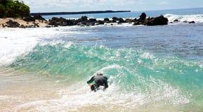 Ein Mann, der am großen Strand in Maui skimboarding ist Stockfoto