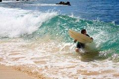 Ein Mann, der am großen Strand in Maui skimboarding ist Lizenzfreies Stockfoto