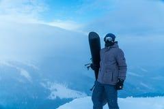 Ein Mann, der in der Hand einen Snowboard hält Snowboarder in den Bergen stockbild
