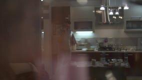 Ein Mann in der Küche spricht an einem Handy Gehen in die Küche und Lösen von Problemen stock video footage