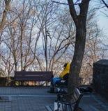 Ein Mann, der kaltem Sitzen auf der Bank sich entspannt auf seiner Jacke glaubt lizenzfreie stockbilder