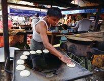Ein Mann, der Kuchen auf Straße in Mandalay, Myanmar kocht Lizenzfreies Stockfoto