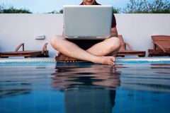 Ein Mann, der an der Laptop-Computer, sitzend am Poolside, selektiver Fokus arbeitet stockbild