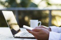 Ein Mann, der mit einem Laptop und einem Handy bei Sonnenaufgang arbeitet Stockbild