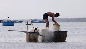 Ein Mann, der mit Netzen auf dem Boot in Nha Trang, Vietnam arbeitet Stockfoto