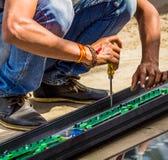 Ein Mann, der mit seinem Schraubenzieherwerkzeug arbeitet Stockbild