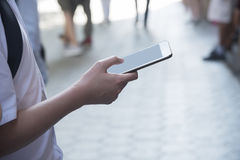 Ein Mann, der ein Mobiltelefon hält Stockbild