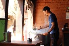 Ein Mann, der Momo bei einem Geschäft, dem südasiatischen oder tibetanischen Mehlkloß dient lizenzfreie stockbilder