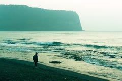 Ein Mann, der morgens das Meer auf den Strand nahe Seongsan Ilchulbong, Jeju-Insel, Südkorea betrachtet Stockfotos