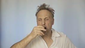 Ein Mann, der nach einer Partei schlecht ist, trinkt Alkohol Er wird vorbei gehangen stock footage