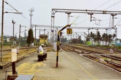 Ein Mann, der nach seinem Zug in der Schienenplattform sucht Stockfotos